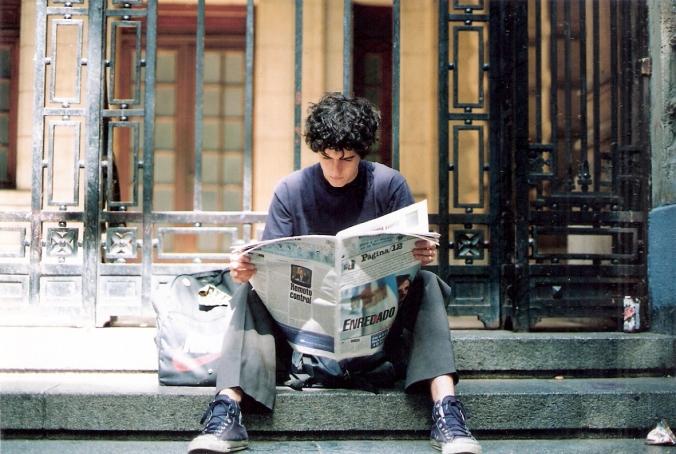 Un joven estudiante lee Página/12 en las escalinatas de su colegio secundario, en 2004
